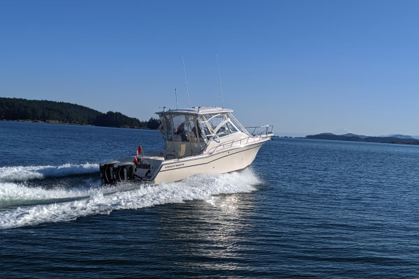 Finshing boat on the move, powered by twin Evinrude engines.