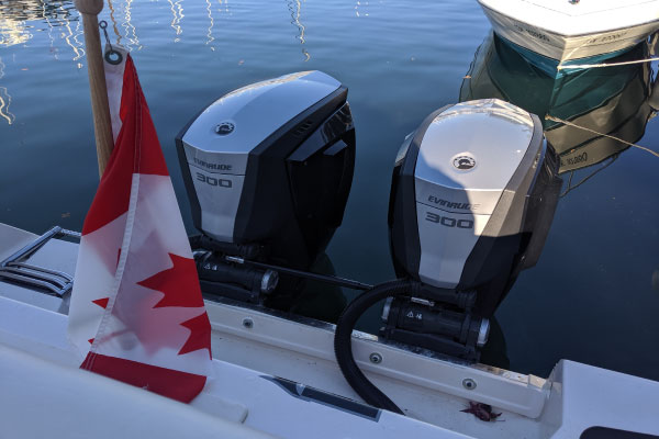 Two Evinrude engines beside Canadian flag idle in water